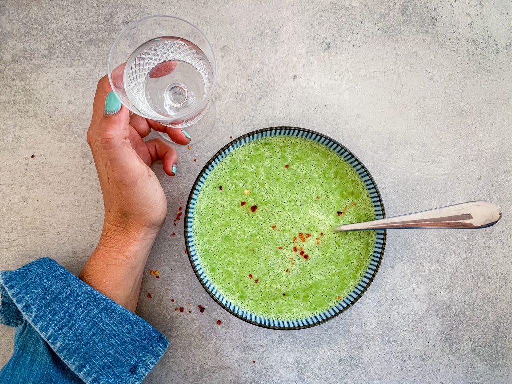 En grön soppa i en skål och en hand som håller i ett glas